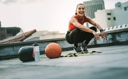 Smiling fitness woman doing sit ups on rooftop stock photo