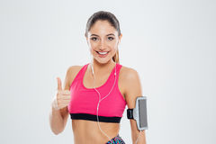 Smiling fitness woman with earphones showing thumb up Stock Images