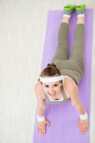 Smiling fitness woman on fitness mat doing yoga Stock Photos