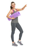 Smiling fitness woman with fitness mat pointing on copy space Royalty Free Stock Image