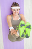 Smiling fitness woman on fitness mat stretching Royalty Free Stock Photo