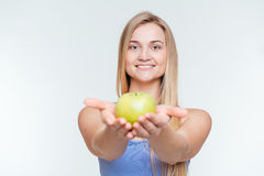 Smiling fitness woman giving apple at camera Stock Photo