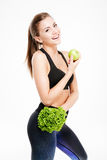 Smiling fitness woman holding apple and lettuce Royalty Free Stock Photos