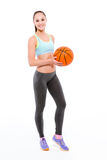 Smiling fitness woman holding basketball ball Royalty Free Stock Image