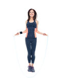 Smiling fitness woman jumping with skipping rope Stock Photography
