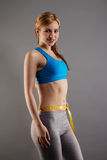 Smiling fitness woman measuring her waist Stock Photo