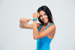 Smiling fitness woman pointing on fitness tracker. Over gray background stock image