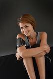 Smiling fitness woman relaxing on dark background Royalty Free Stock Image