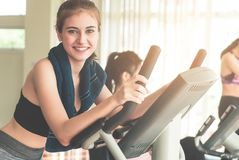 Smiling Fitness woman is running on treadmill with friends. Smiling Fitness women is running on treadmill with friends on background Stock Photography