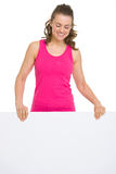 Smiling fitness woman showing blank billboard Royalty Free Stock Photo