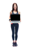 Smiling fitness woman showing laptop screen. Full length portrait of a smiling fitness woman showing laptop screen isolated on a white background. Looking at Stock Photo