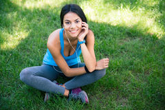 Smiling fitness woman sitting on the green grass. Smiling beautiful fitness woman sitting on the green grass outdoors and looking at camera Royalty Free Stock Photography