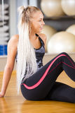 Smiling fitness woman sitting in workout outfit at the gym Royalty Free Stock Photos
