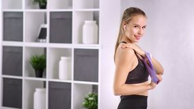 Smiling fitness woman training shoulder muscle using rubber band at home medium shot