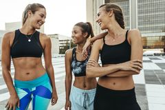 Smiling fitness women out on street for morning jog. Smiling fitness women in training wear talking to each other standing on a street. Three women joggers stock photography