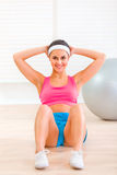 Smiling fitness young girl doing abdominal crunch Stock Images