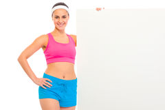 Smiling fitness young girl holding blank billboard Stock Photos