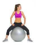 Smiling fitness young woman on fitness ball looking on copy space Royalty Free Stock Image