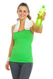 Smiling fitness young woman giving bottle of water Royalty Free Stock Image