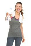 Smiling fitness young woman giving bottle of water Royalty Free Stock Photography