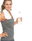 Smiling fitness young woman holding bottle of water. Isolated on white Royalty Free Stock Photos