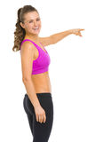 Smiling fitness young woman pointing on copy space Stock Photography