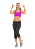 Smiling fitness young woman pointing up on copy space Stock Photography