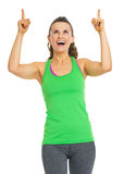 Smiling fitness young woman pointing up on copy space Royalty Free Stock Photo