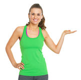 Smiling fitness young woman presenting something on empty palm Stock Image