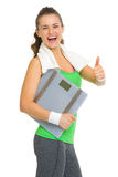 Smiling fitness girl with scales showing thumbs up Stock Photography