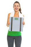 Smiling fitness young woman showing scales Stock Photography