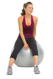 Smiling fitness woman sitting on fitness ball Royalty Free Stock Images