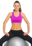 Smiling fitness young woman sitting fitness ball Royalty Free Stock Photos