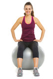 Smiling fitness young woman sitting on fitness ball Stock Images