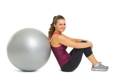 Smiling fitness young woman sitting near fitness ball Stock Photography
