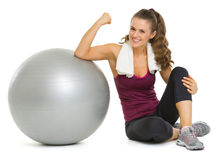 Smiling fitness woman sitting near fitness ball Royalty Free Stock Photo