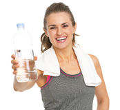 Smiling fitness young woman with towel giving bottle of water Royalty Free Stock Image