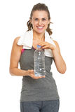 Smiling fitness young woman with towel showing bottle of water Royalty Free Stock Photo