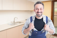 Smiling fitter acting like a superhero. Smiling fitter with spanner acting like a superhero in the kitchen with advertising area Royalty Free Stock Photography