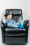 Smiling five year old boy dressed up in a pirate and police officer costume sit and laze in an black leather armchair. Stock Image