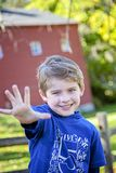 Smiling five year old boy holding out five fingers. Smiling, happy five year old boy wearing five shirt and holding out five fingers stock images