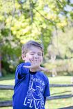 Smiling five year old boy holding out five fingers. Smiling, happy five year old boy wearing five shirt and holding out five fingers royalty free stock images