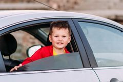 Smiling five-year-old boy looks out of the open car window royalty free stock photos
