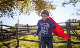 Smiling five year old boy running with red cape outside stock photography