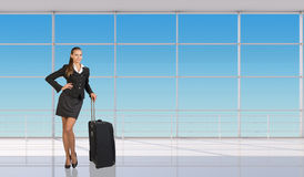 Smiling flight attendant standing with luggage Stock Photography