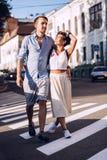 Smiling flirting woman and man walking on crosswalk Royalty Free Stock Images