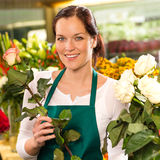 Smiling florist cutting rose flower shop woman Stock Photo