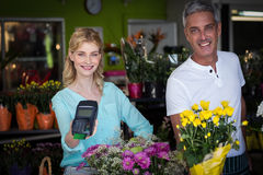 Smiling florist showing credit card terminal in flower shop Royalty Free Stock Photography