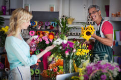Smiling florist spraying water on flowers in flower shop Stock Image