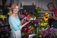 Smiling florist spraying water on flowers in flower shop Stock Photos